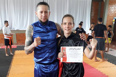 Elisa Dill, estudante da UNILA, com seu Mestre Anderson Torres, recebendo a certificação de faixa vermelha de Kung Fu