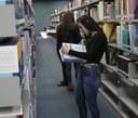 estudantes consultam livros na biblioteca