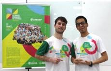 Raime Rodríguez e Carlos Ramos junto a um banner com a logotipo e informações do 9º Torneio Paranaense de Economia