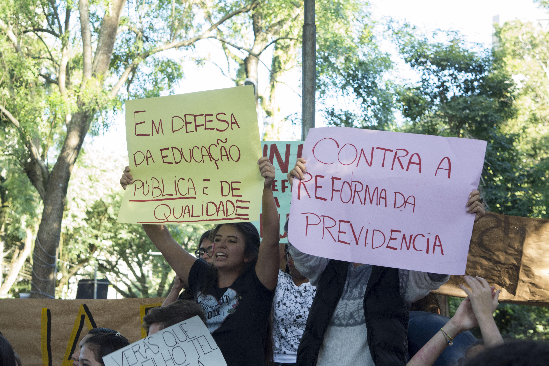 Duas jovens seguram cartazes com dizerem em defesa da educação