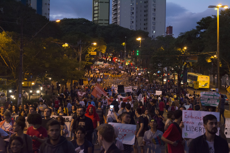 Dezenas de pessoas com cartazes em defesa da educação pública e gratuita