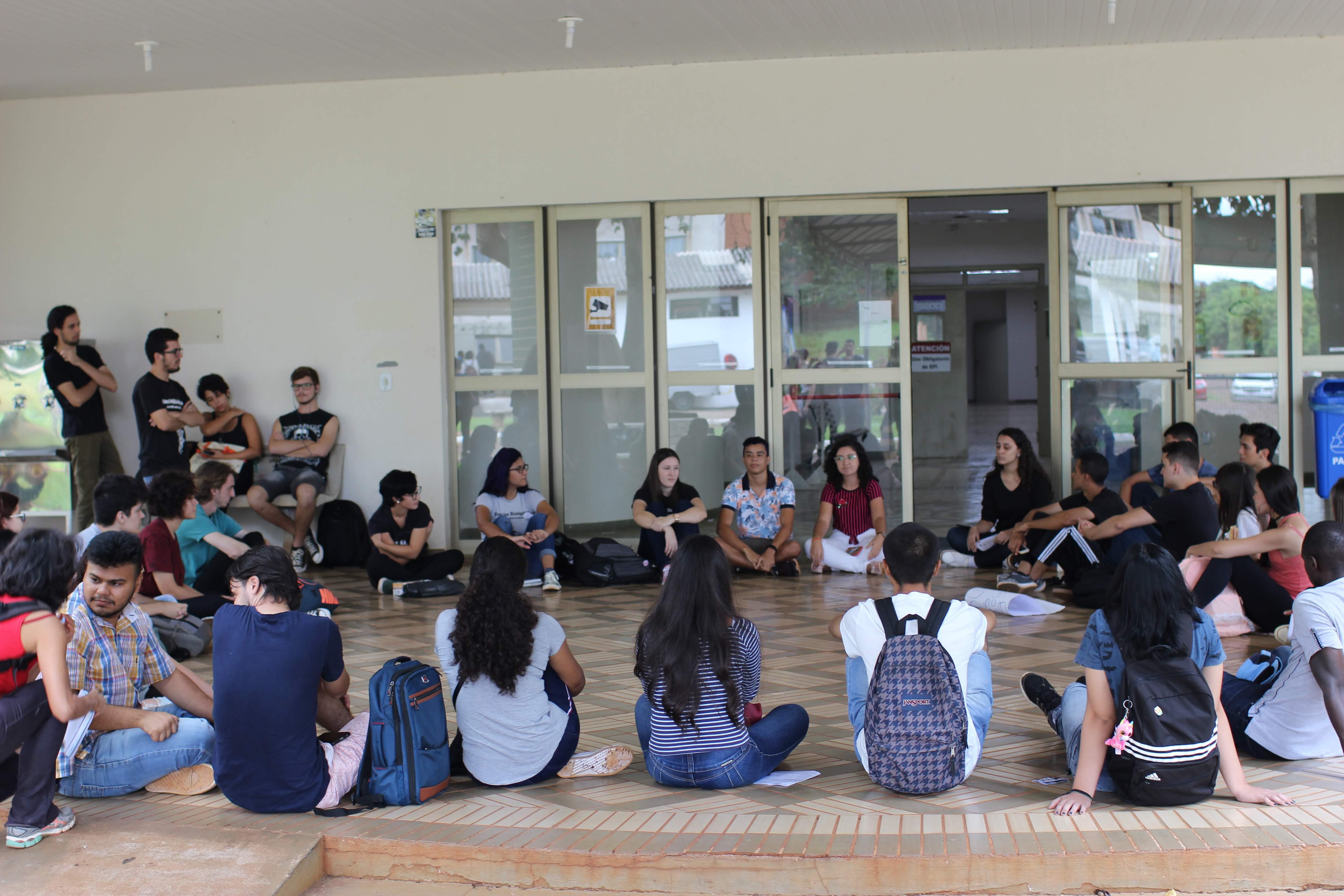 Jovens sentados no chão, formando uma roda, conversam em frente à entrada de laboratórios da UNILA