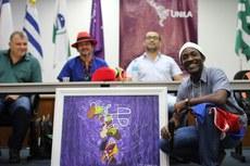 Dady Simon, artista haitiano, com quadro pintado por ele à frente da mesa onde estão coordenadores de cursos da UNILA