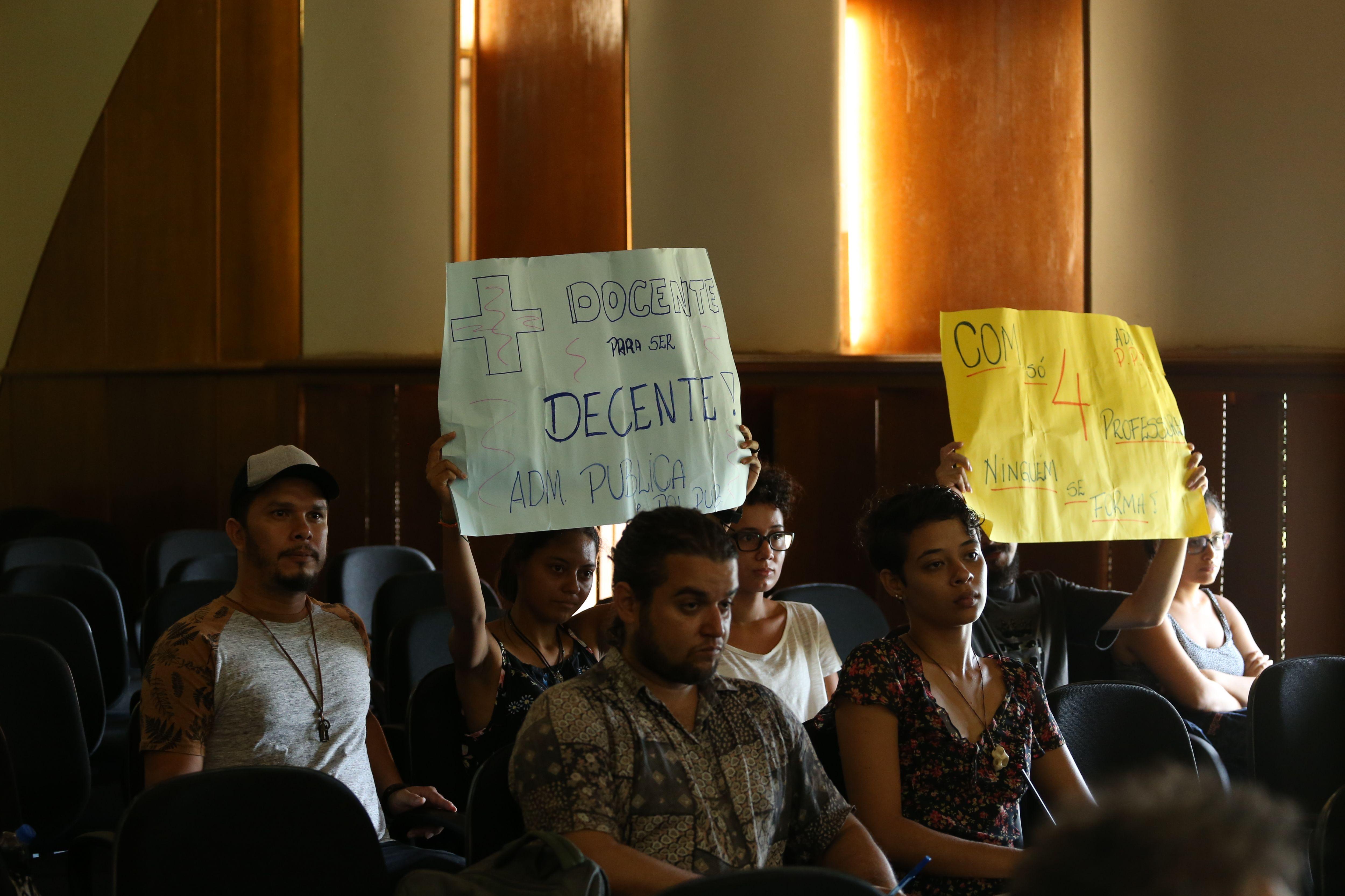 Estudantes sentados no auditório seguram cartazes pedindo mais professores para o curso de Administração Pública