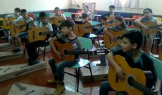 Crianças em sala de aula, aprendendo a tocar violão