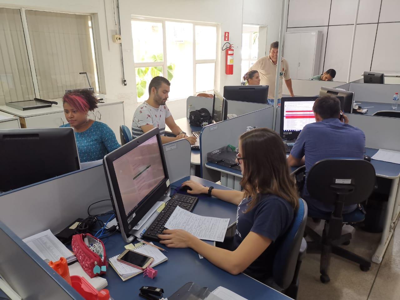 Camila (em primeiro plano), Olga (de camiseta azul) e Roberth (de camiseta branca) se encarregam do trabalho de acompanhamento de casos suspeitos