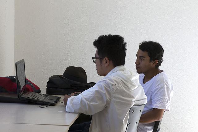 Dois jovens observam tela de computador