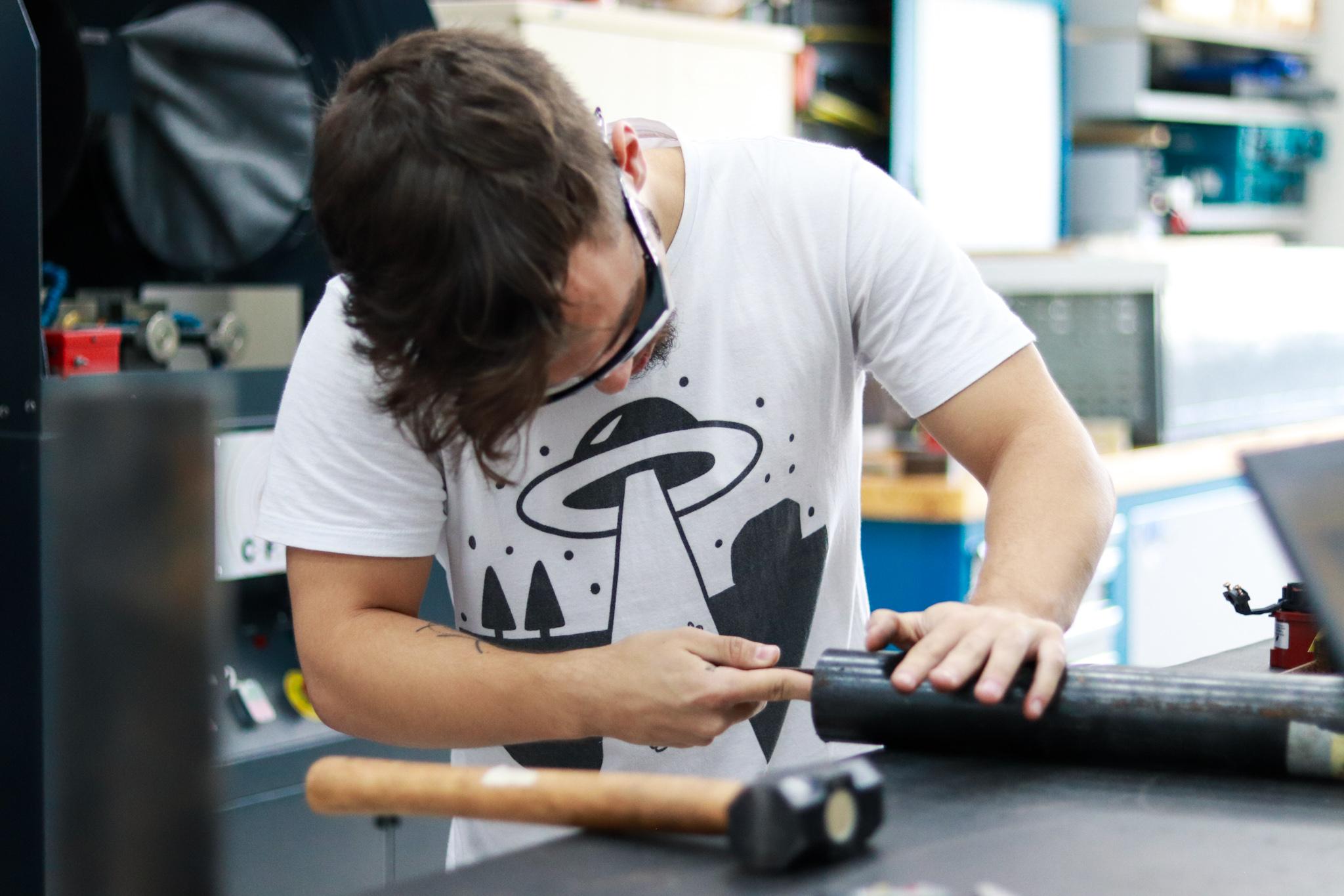 Jovem usa uma lixa para lixar um objeto de metal cilíndrico colocado sobre uma mesa