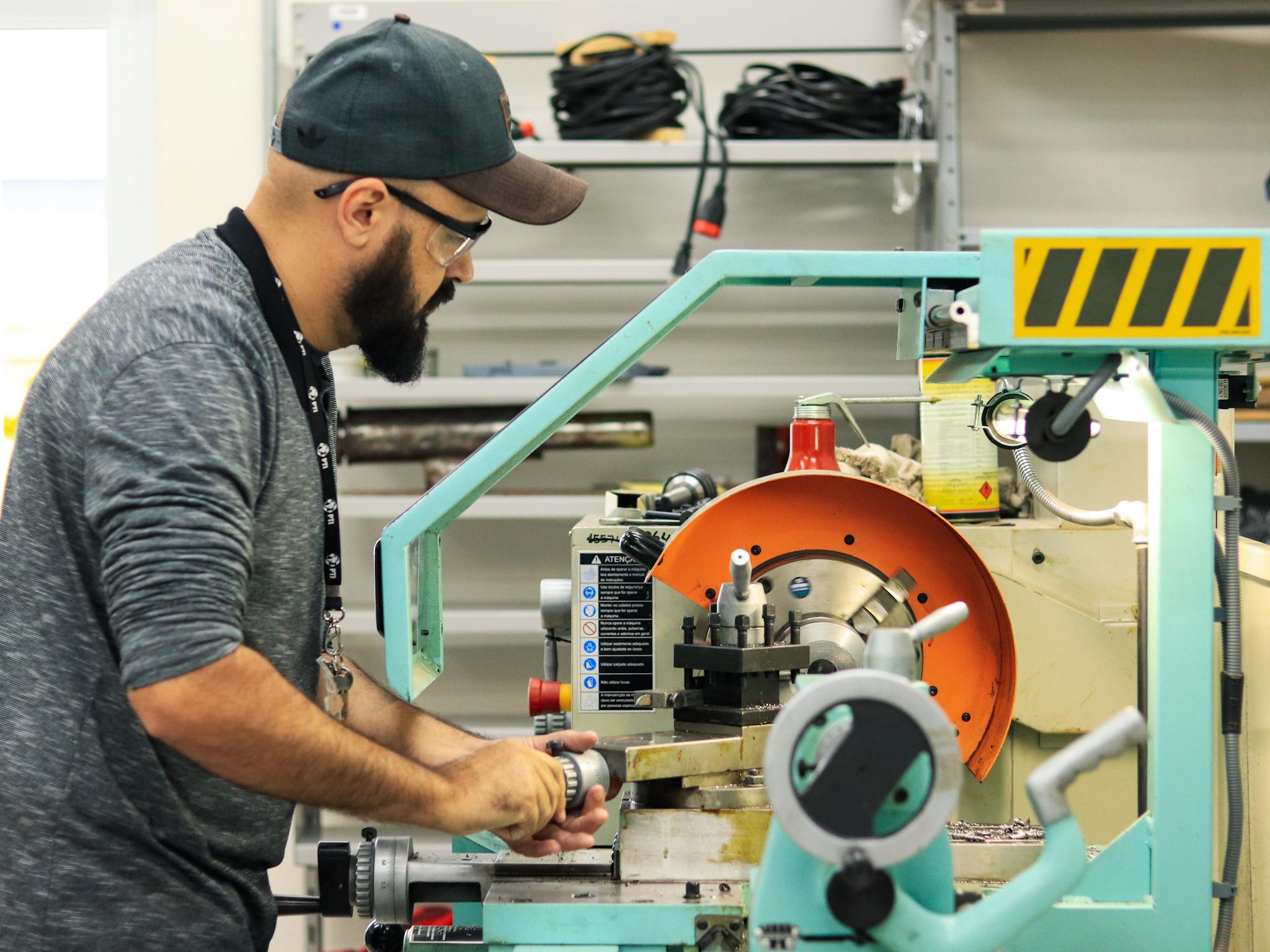 Jovem trabalha com uma peça de metal, cilíndrica, em uma máquina colocada numa bancada