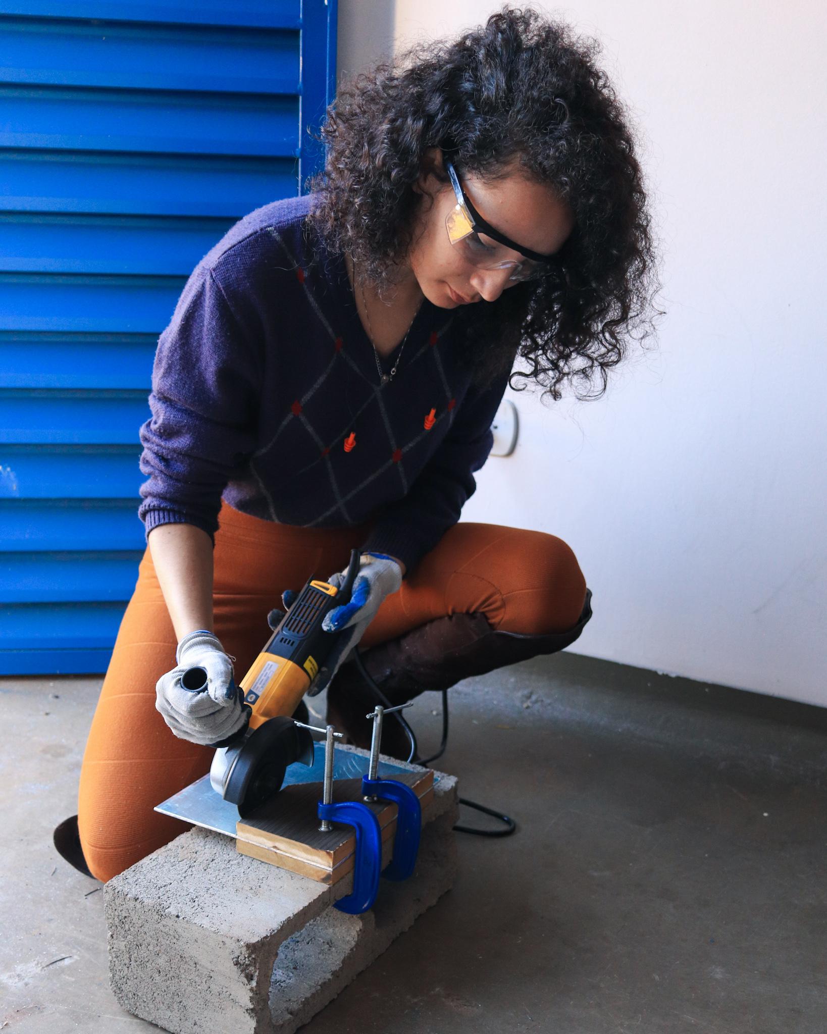 Jovem usa serra manual para cortar um pedaço de metal