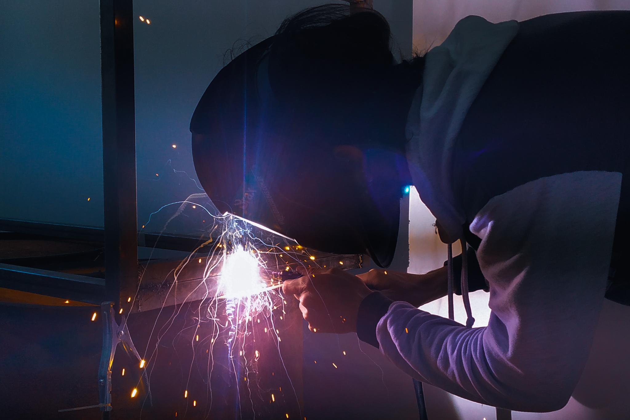 Pessoa com capacete e maçarico soldando peça de metal