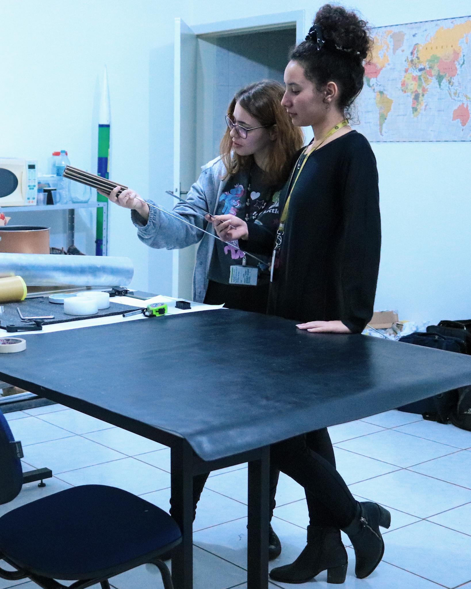 Duas jovens em pé, junto a uma mesa, observam um objeto cilíndrico