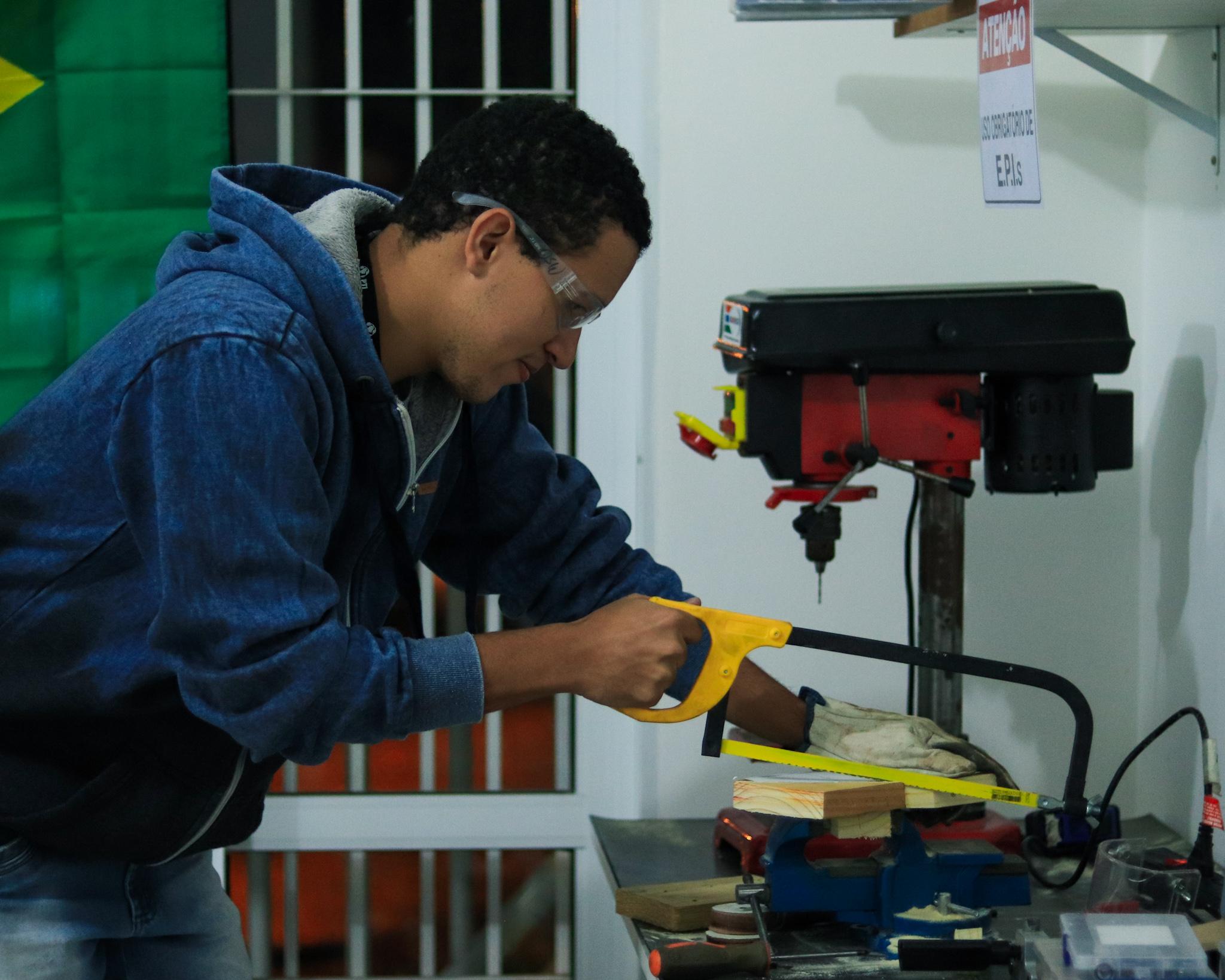 estudante corta um pedaço de madeira com uma serra