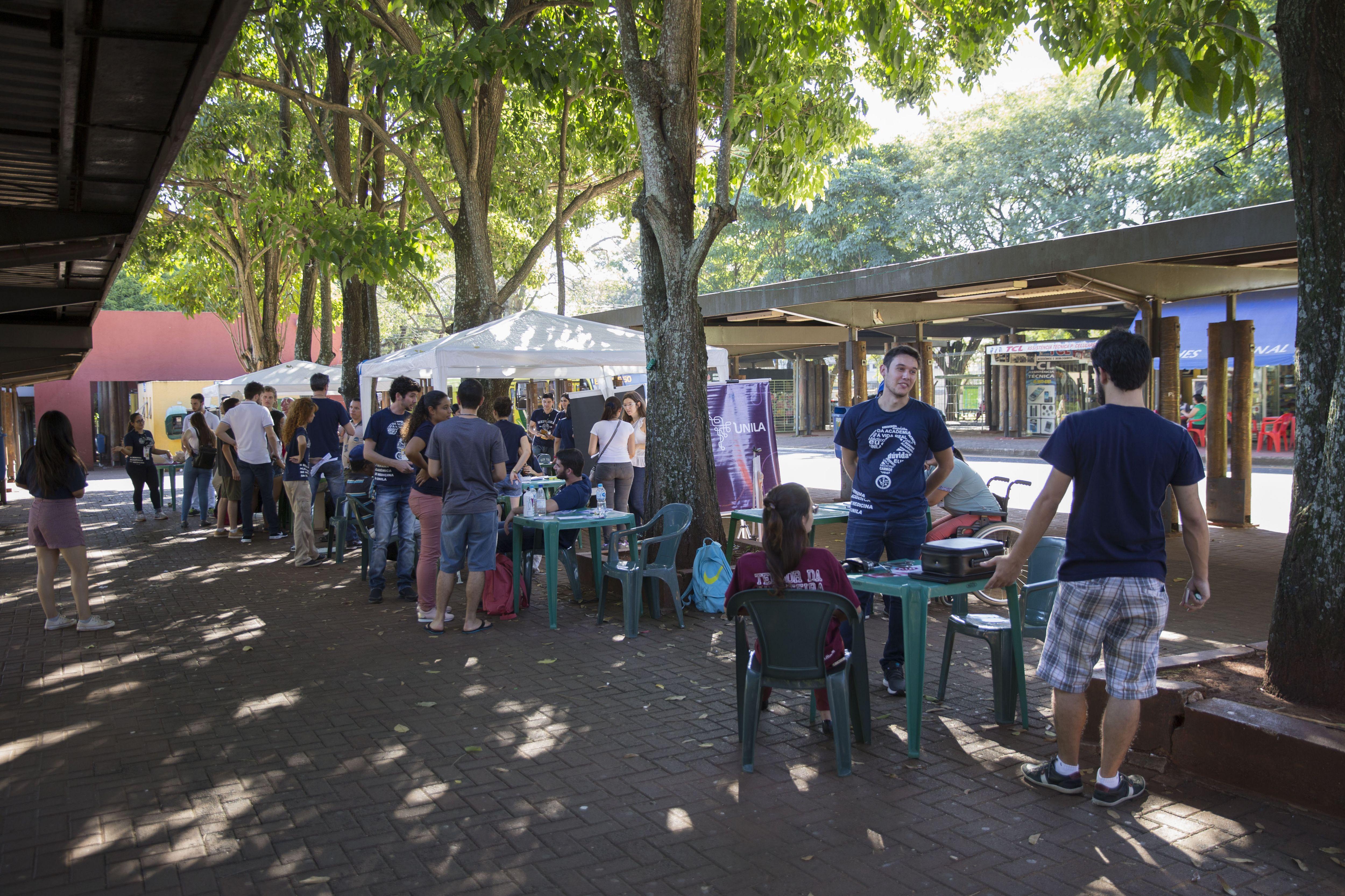 imagem mostra mesas onde estudantes orientam usuários do terminal urbano