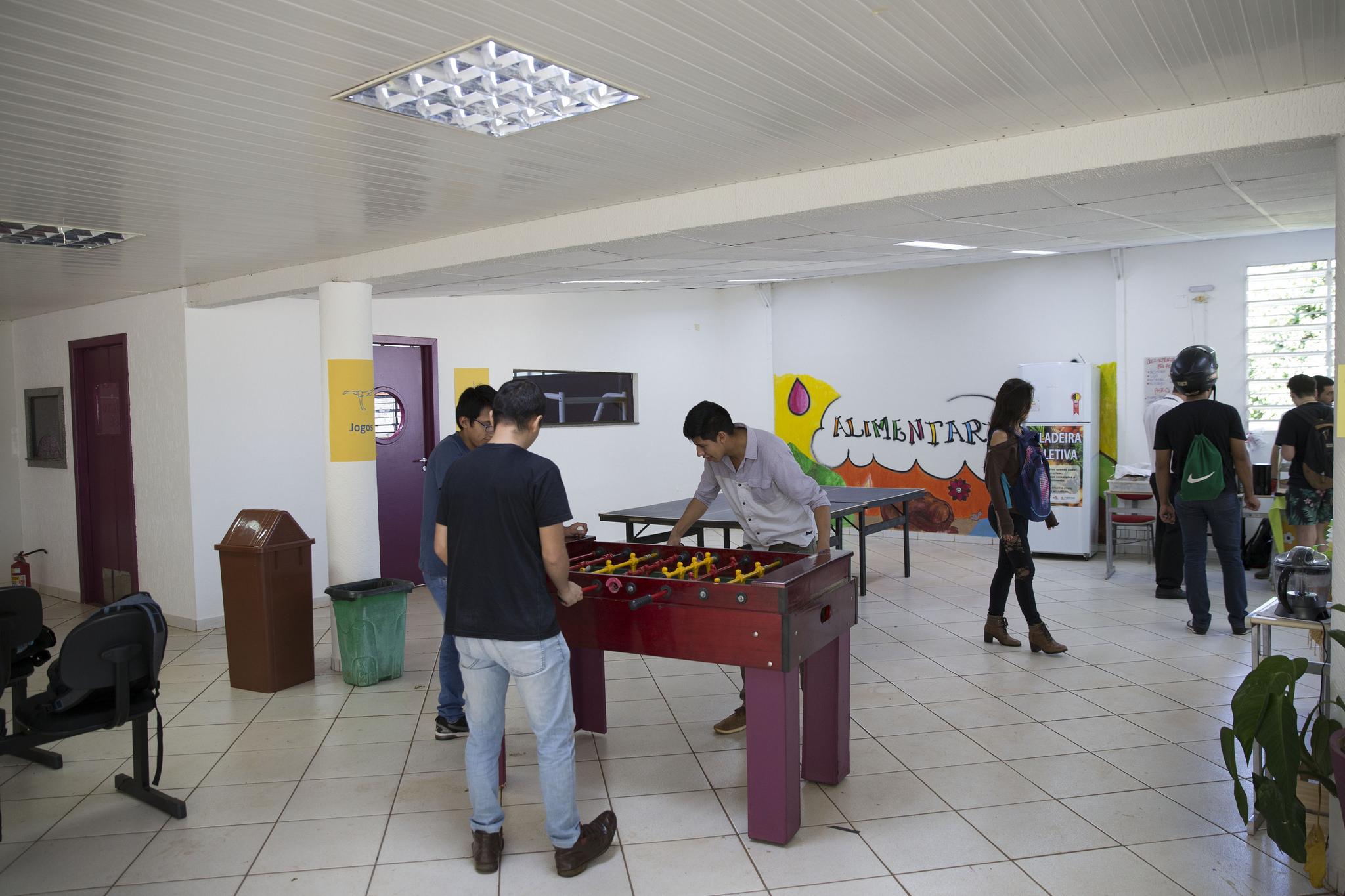 Jovens brincam em mesa de pebolim