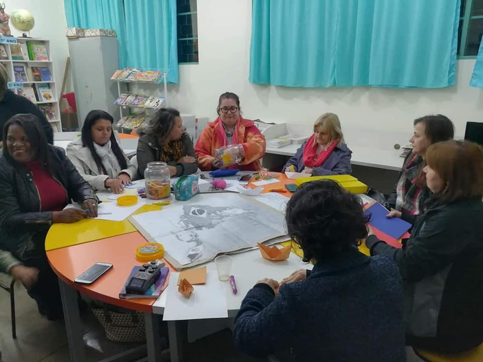 Professoras sentadas em círculo em uma sala de aula