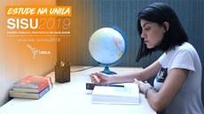 Uma jovem, sentada a uma mesa, lê e tem ao lado um globo terrestre