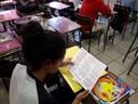 Estudante lê folheto distribuído durante apresentação do projeto Unila ao seu Alcance