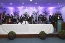 Formandos sentados em cadeiras no palco de um teatro; num nível inferior, mesa com autoridades da universidade; estudante faz discurso, em pé, à direita na foto